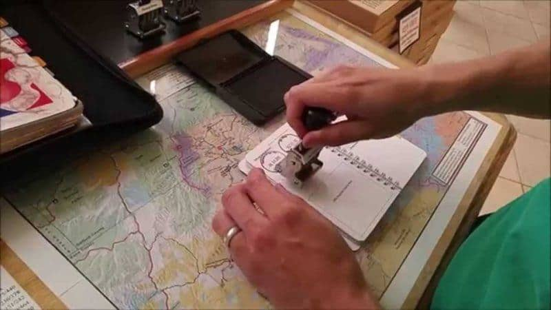 Demonstrating how the national park stamp cancellation process is done.