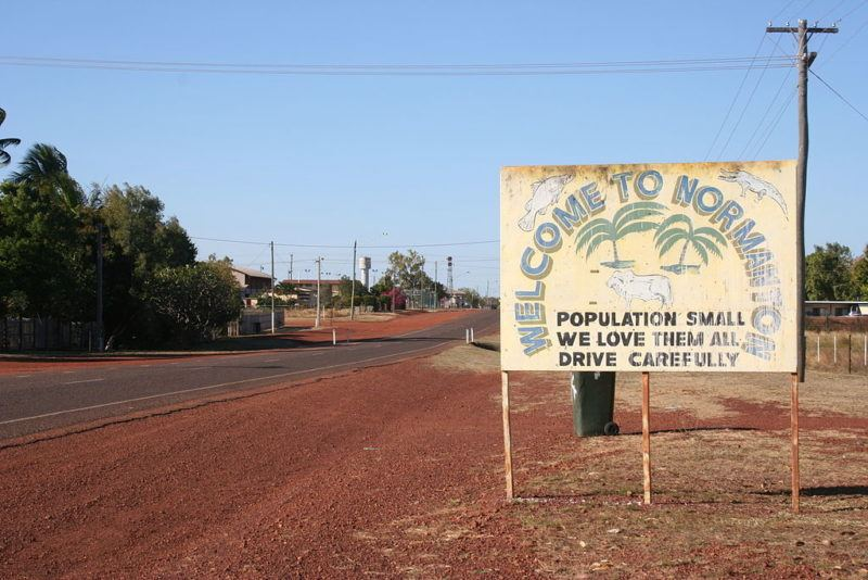 Sign along the road outside one of the towns in the Australian outback. Says Welcome to Normanton Population small we love them all. Drive Carefully.
