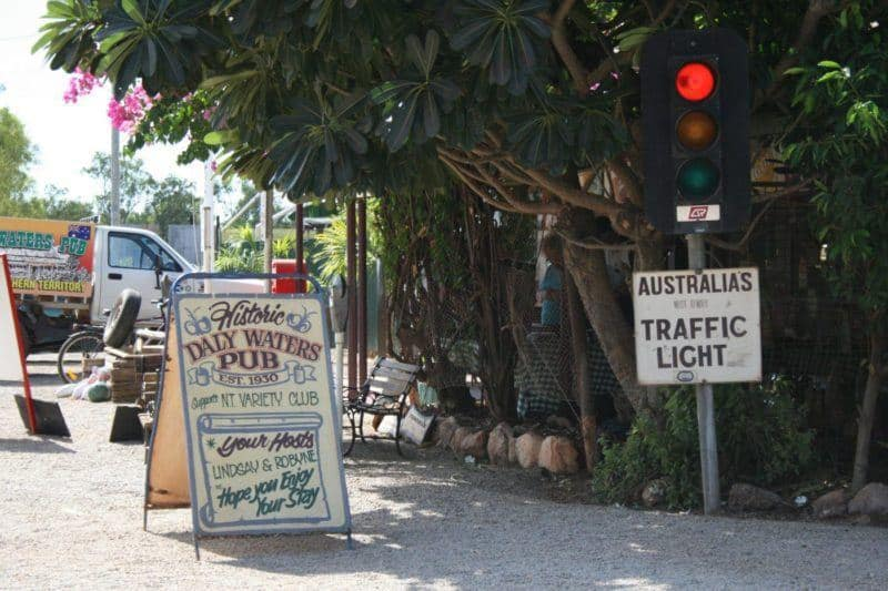 Australian outback town sign says Historic Daly Waters Pub est. 1930. Nearby stoplight says Australia's most remote traffic light.