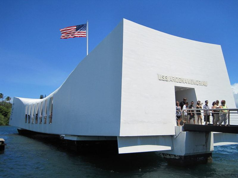 American flag flies atop the USS Arizona Memorial at Pearl Harbor. At right, tourists exit the building.