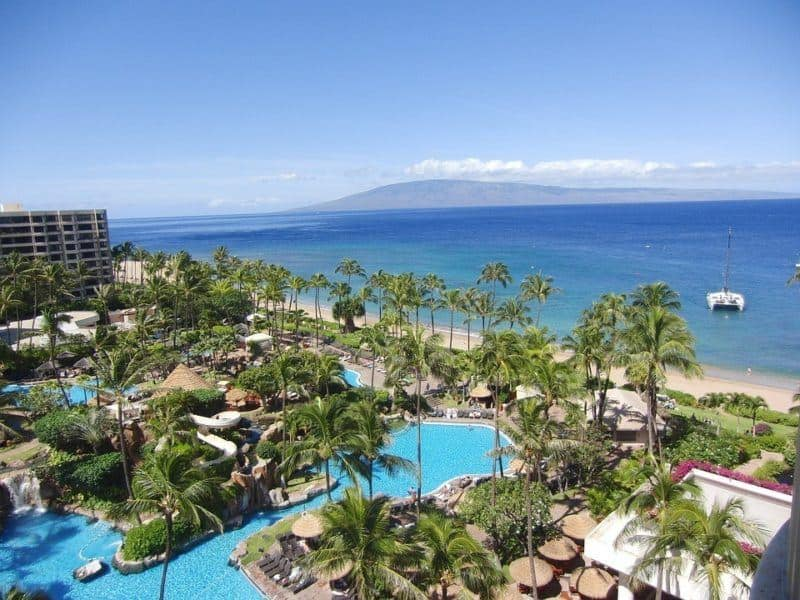 Pool, palm trees, sandy beach and ocean at a Hawaii resort. Mountain in background.